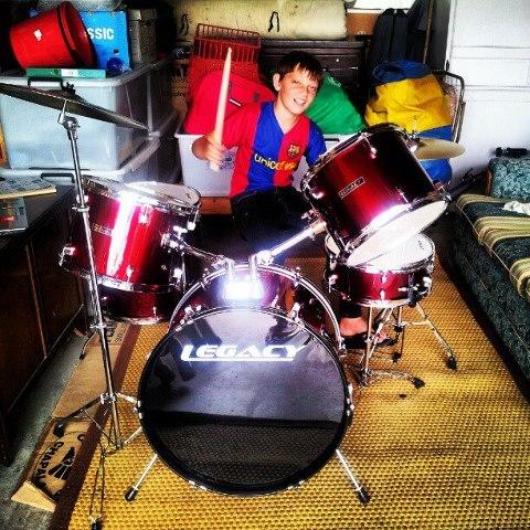 Boy drumming on red drum kit