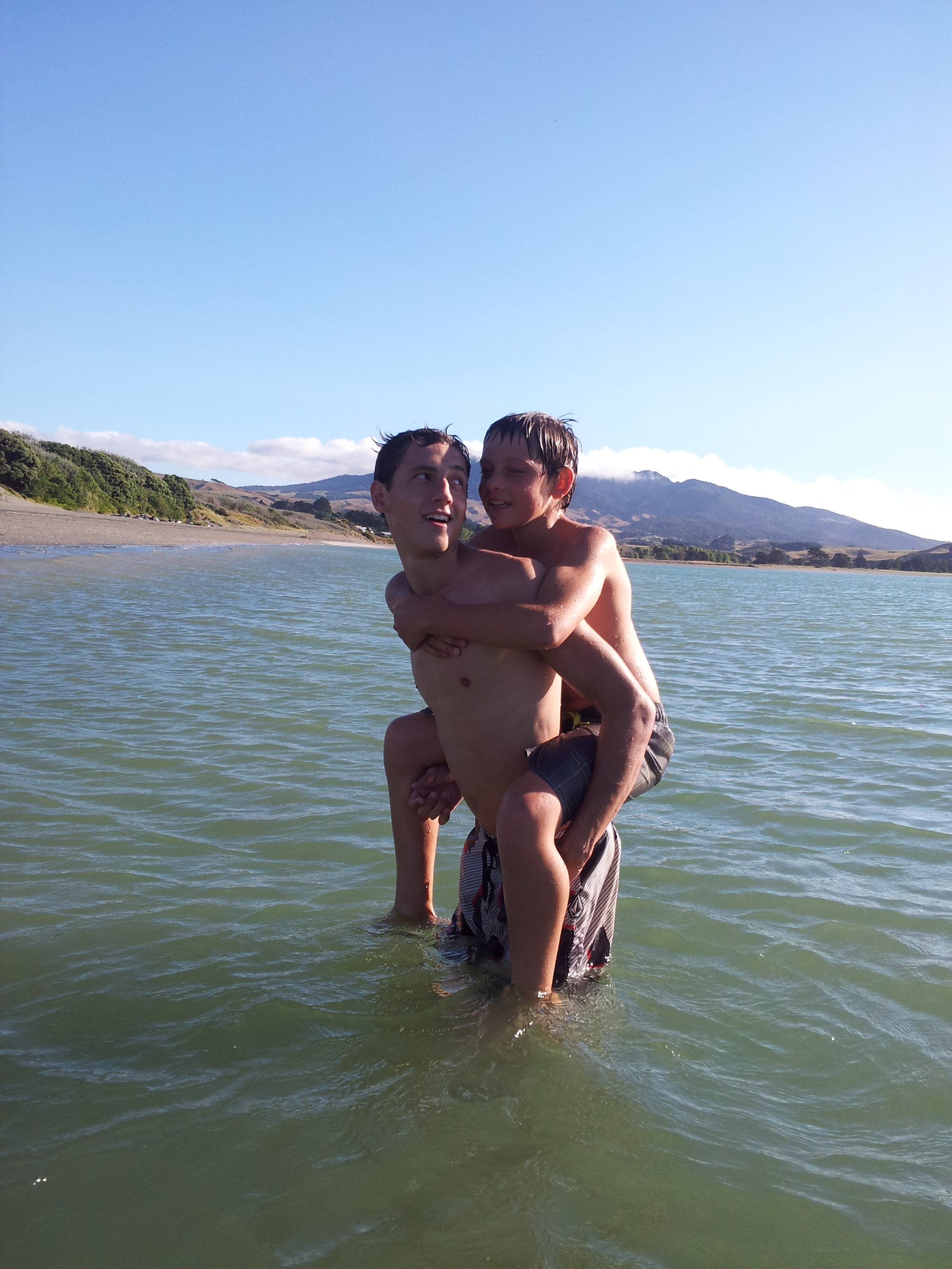 Boys in ocean with mountain in background