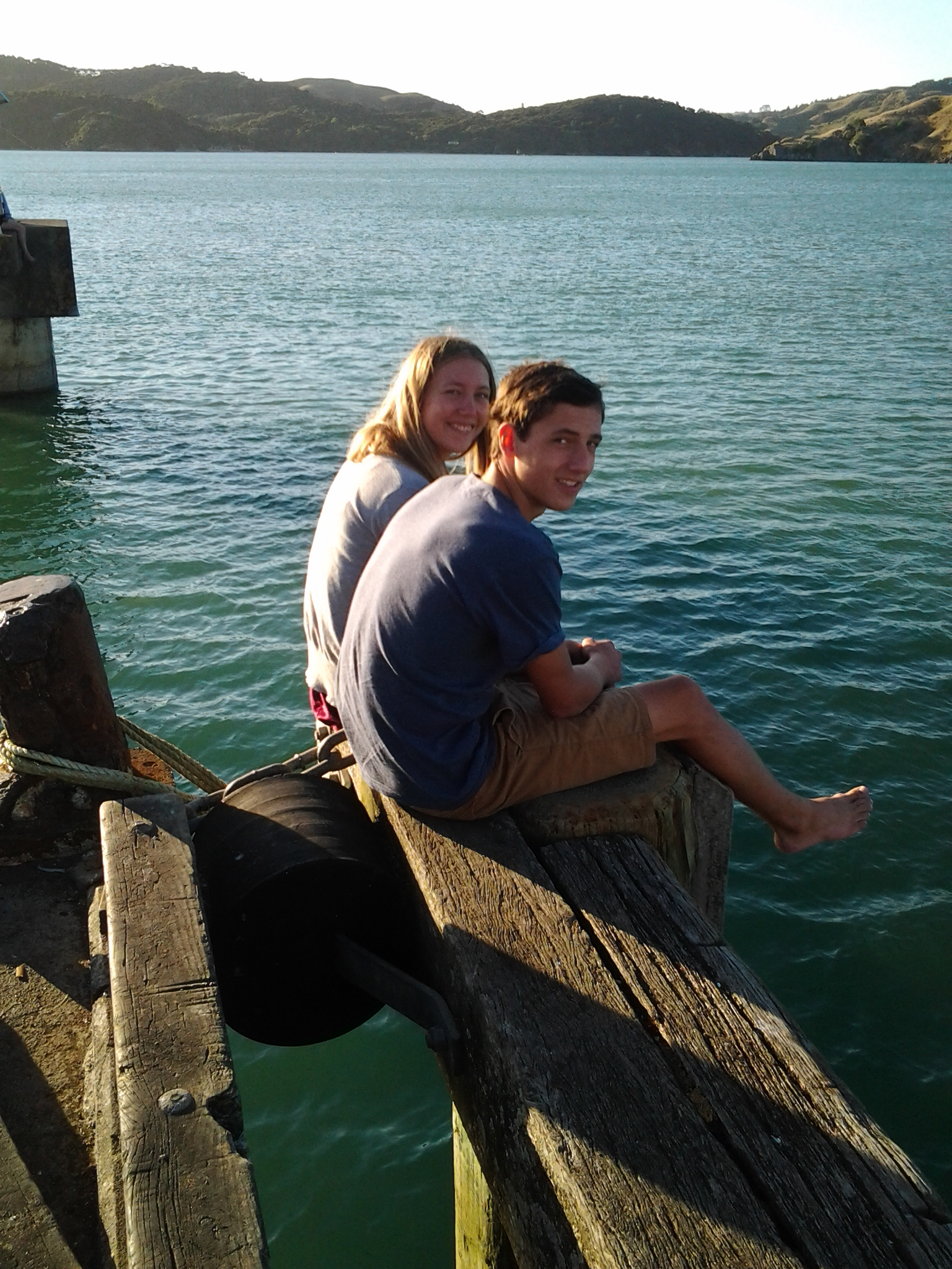 two people sitting on the end of the wharf