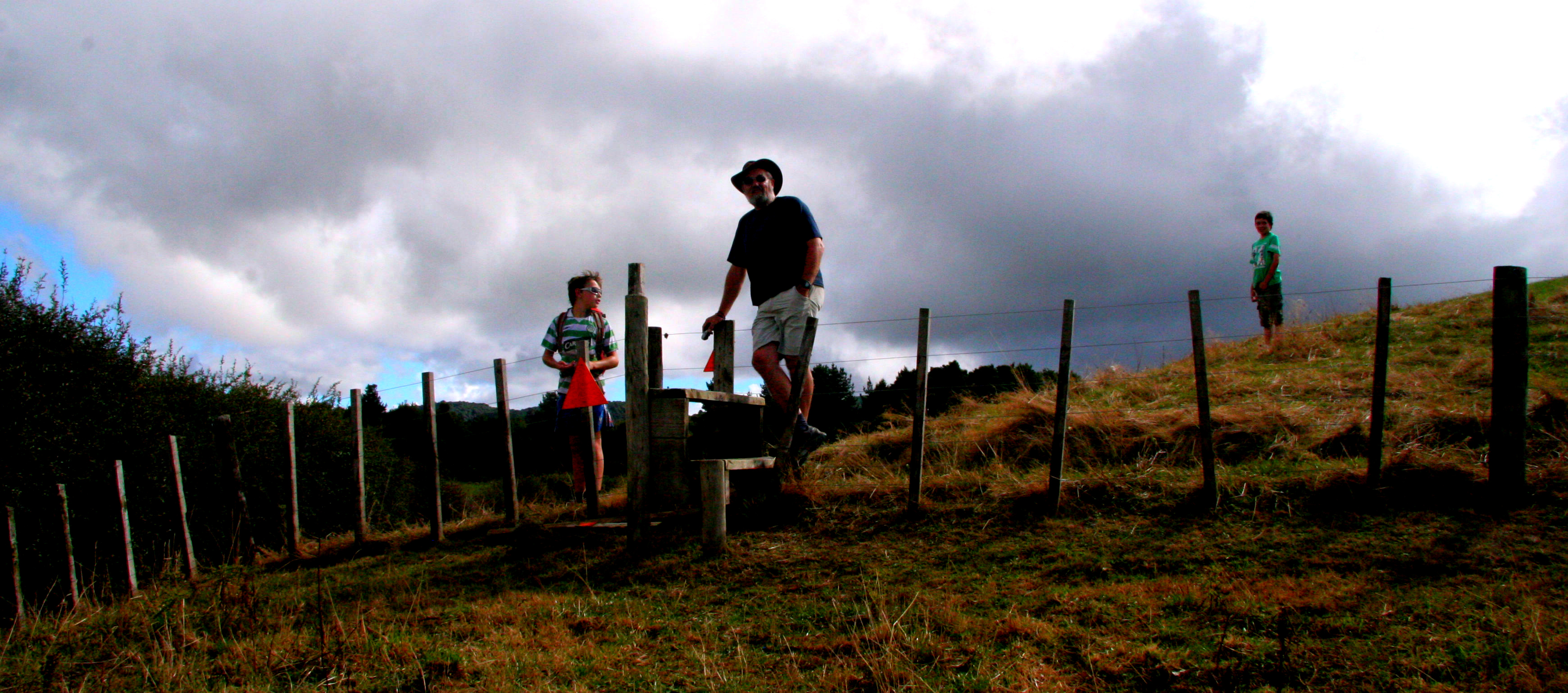 A man and a boy standing by a fence in a paddock on a hillside