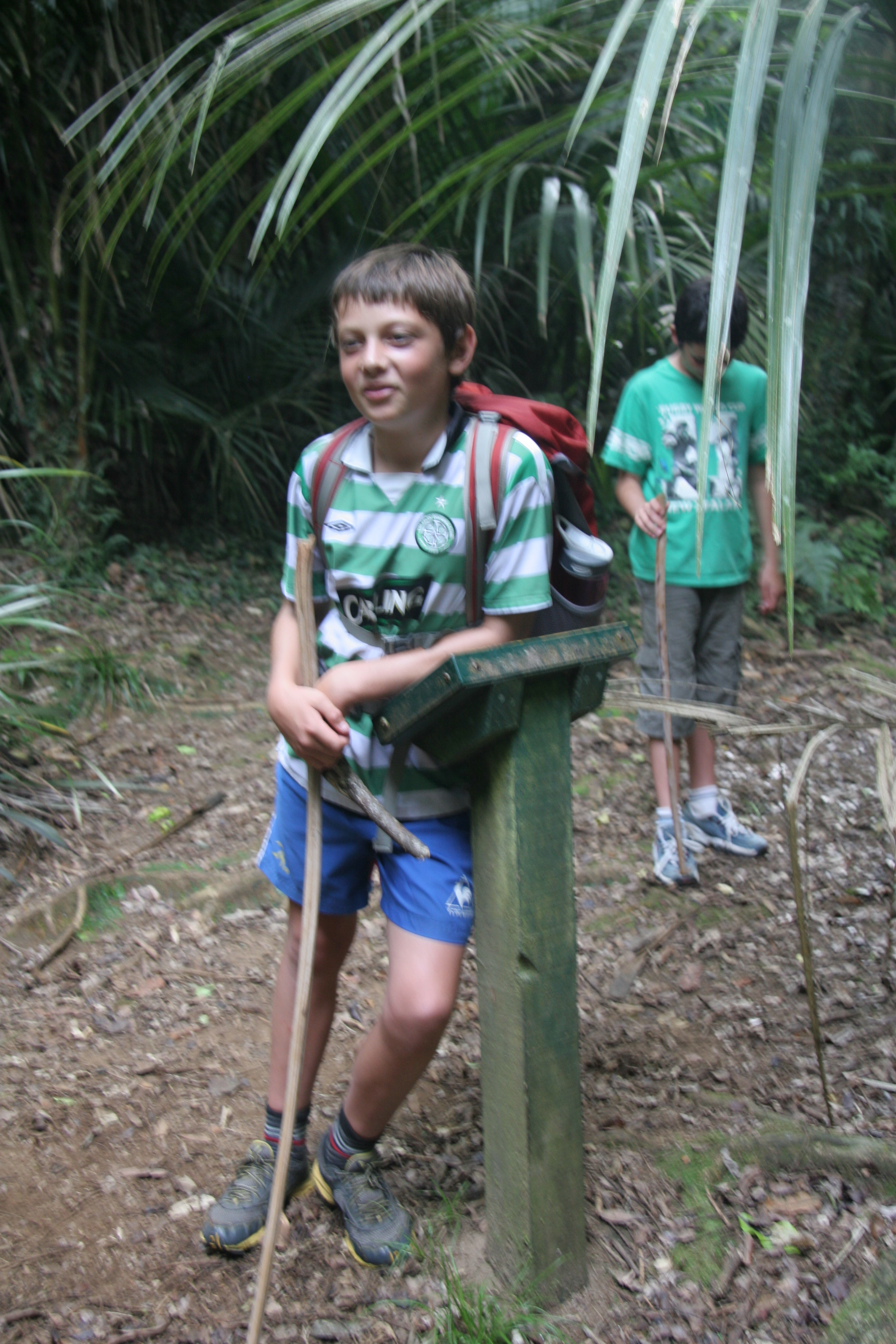 Boy leaning on signpost in bush