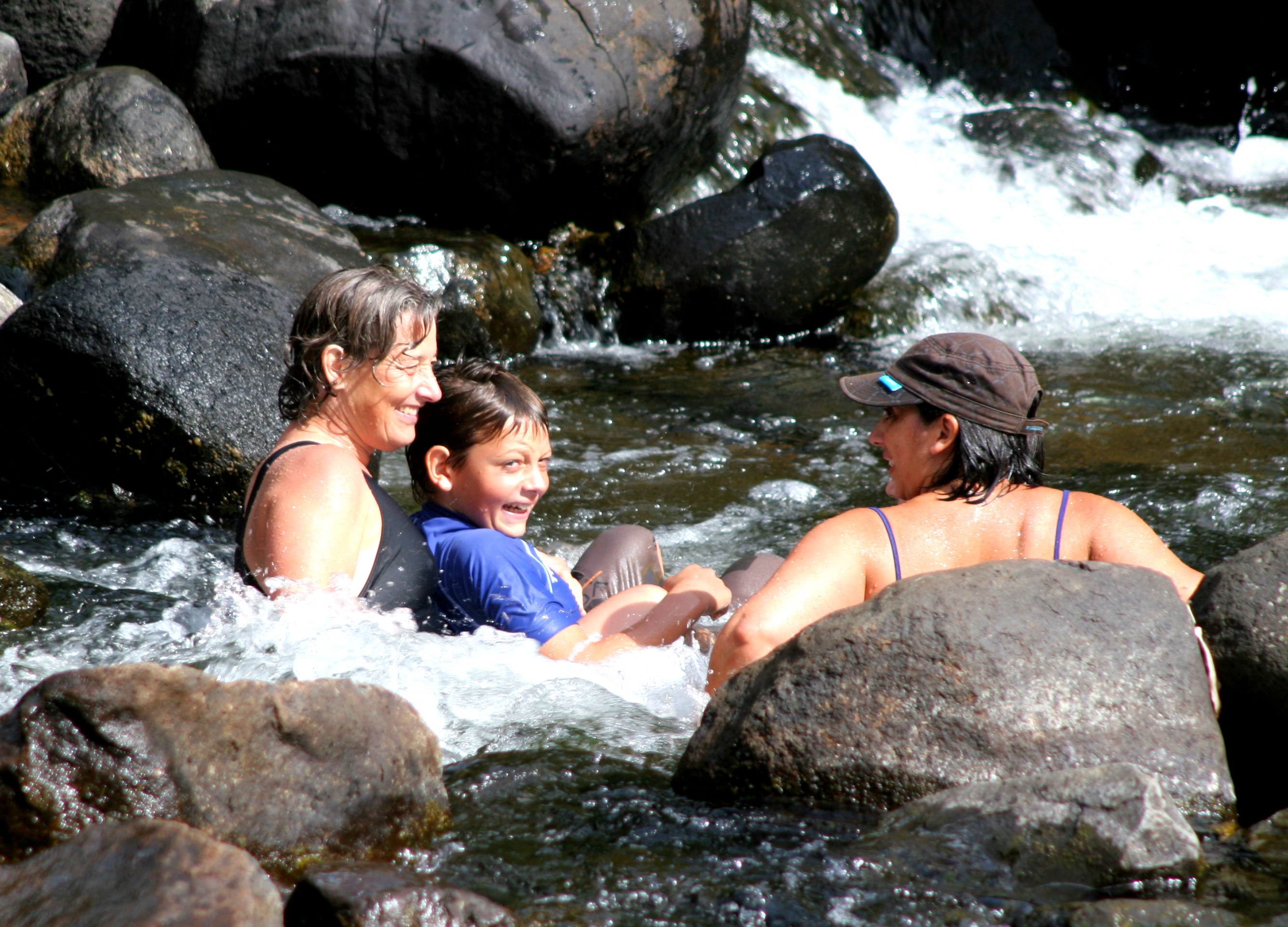 Two women and a child sitting in the flowing water of a river.  Rocks and boulders around them.