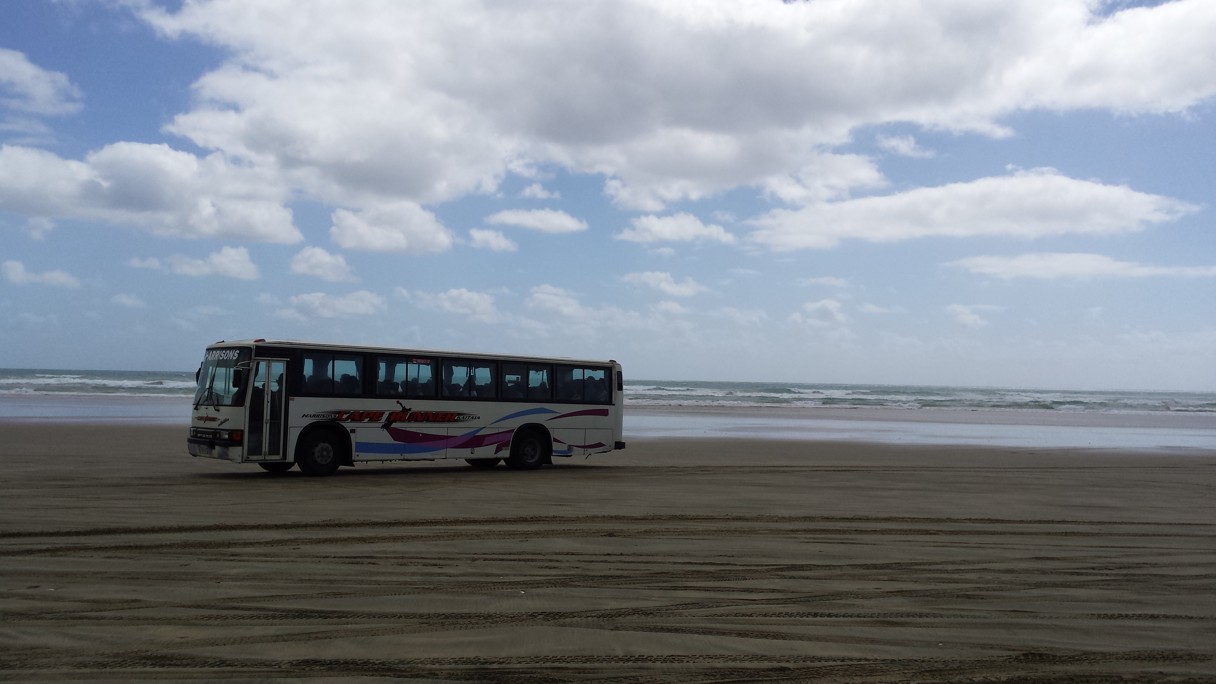 Tour bus travelling alon 90 Mile Beach with the Tasman Sea in the background