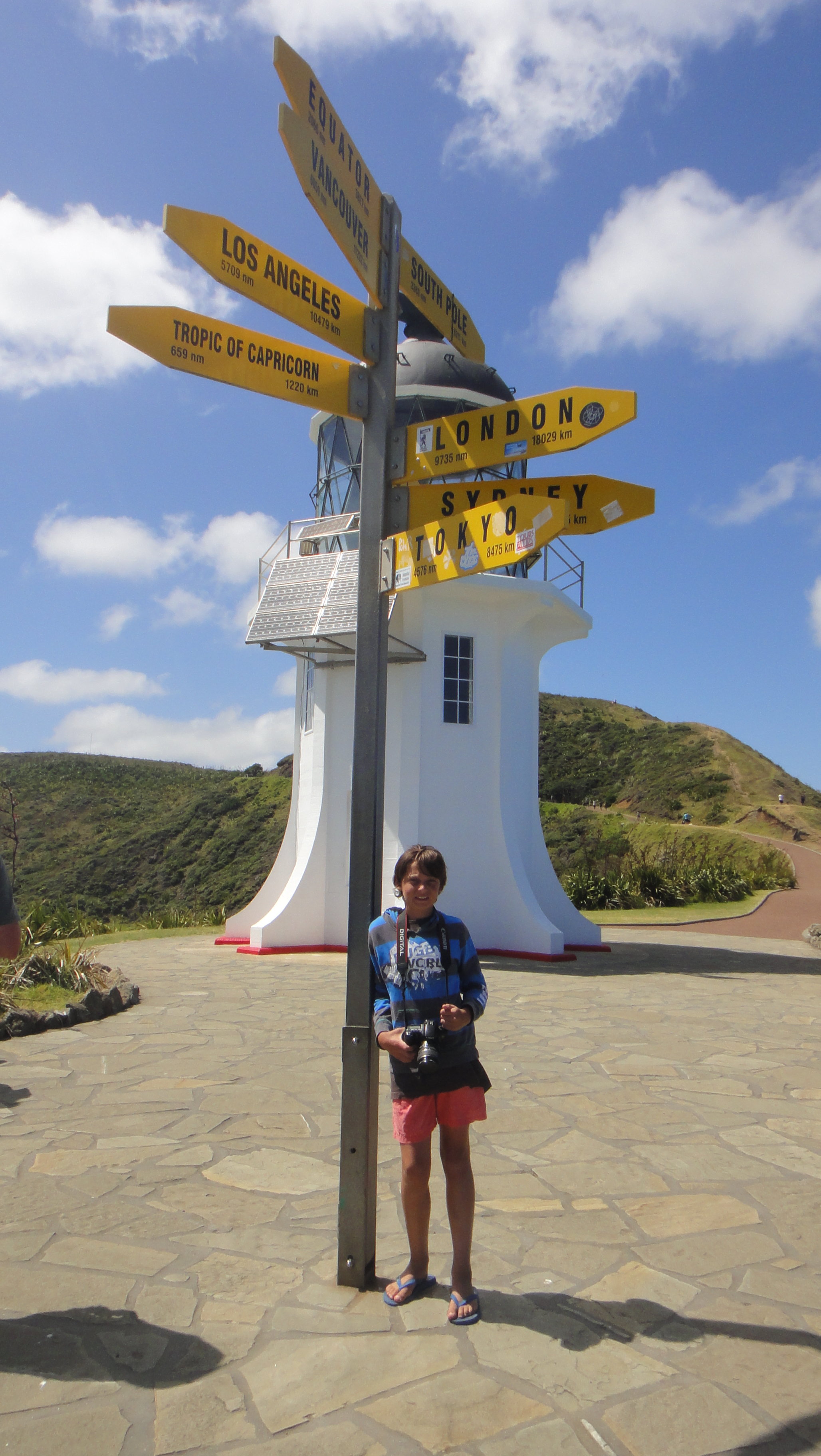 teenage boy standing in front of signpost showing directions to all parts of the world.  White lighthouse in the background, clear, blue sky. This is the lighthouse at Cape Reinga, the northernmost tip of New Zealand.