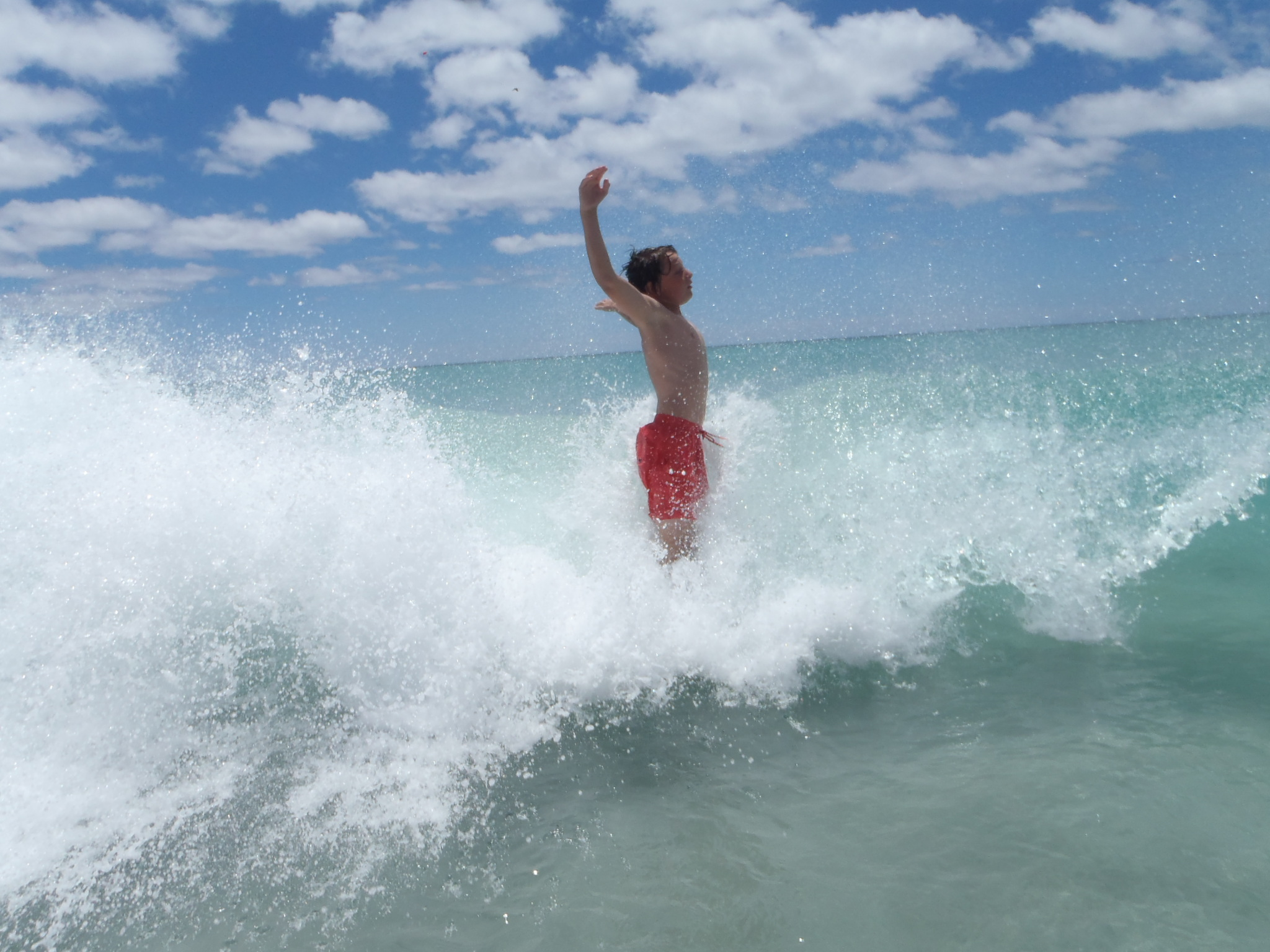 Boy jumping in the waves.  Clear blue sky. Beautiful summer day.