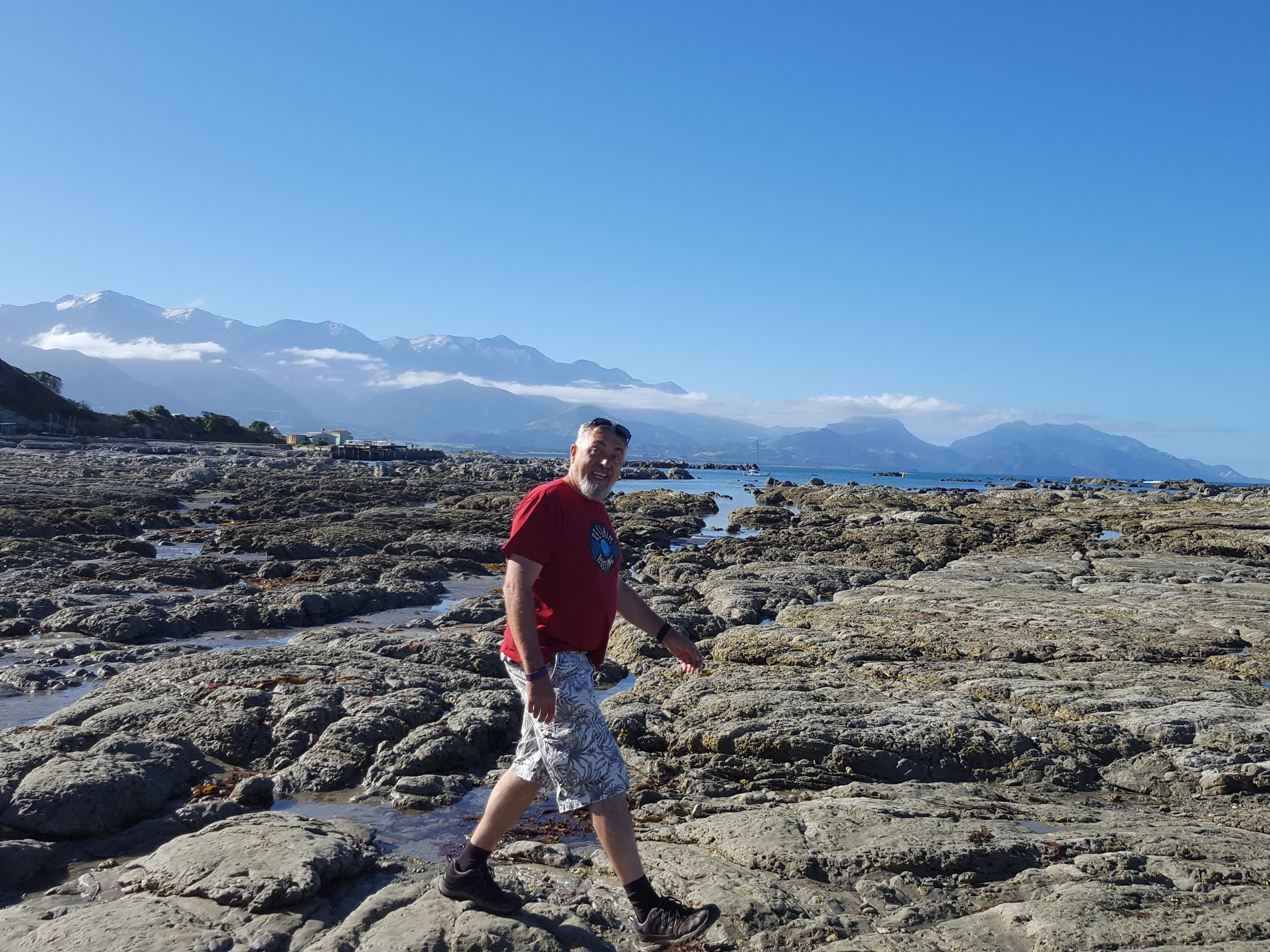 man wearing a red tee short and shorts walking across the rocky beach area at the coast. Mountains in the background with wisps of cloud in front of them.