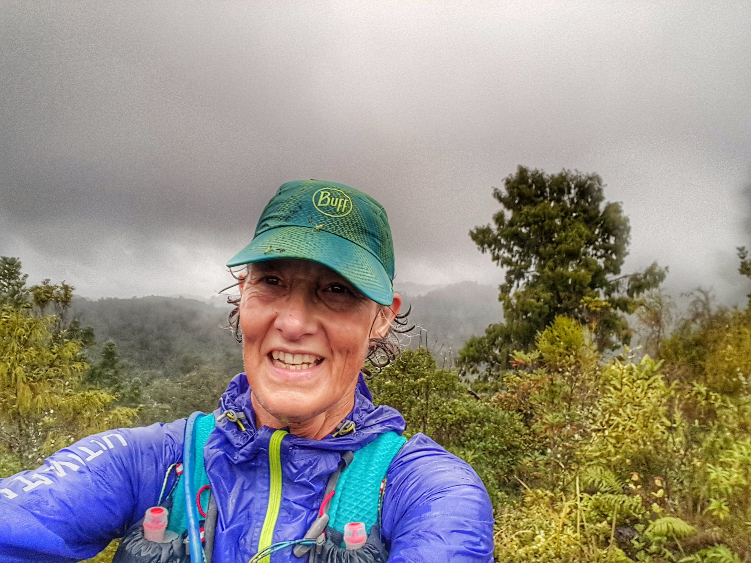 female trailrunner, wearing turquoise cap and purple rain jacket. Self portrait at the top of a hill in the rain with dark clouds and forested valley in the background