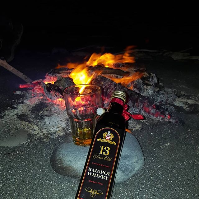 fire on the beach with a glass and a bottle of whisky in the foreground
