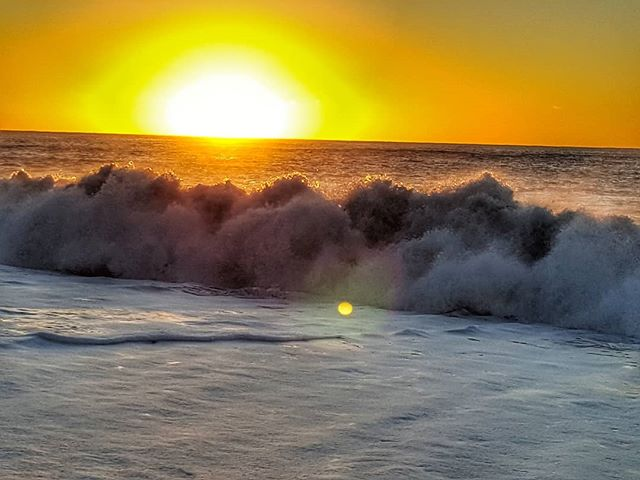sunrising over the ocean, turbulent waves in the forground