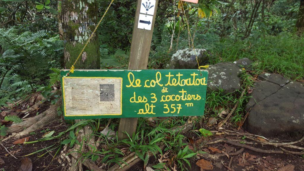 """signpost that reads """"le col tetoatoa dit des 3 cocotiers alt 357m'"""