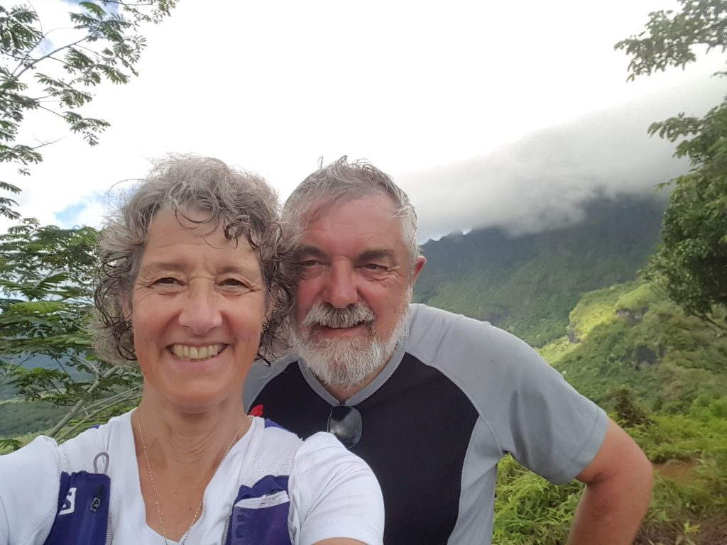 A couple at the top of a mountain, clouds gathering atop a mountain in the background